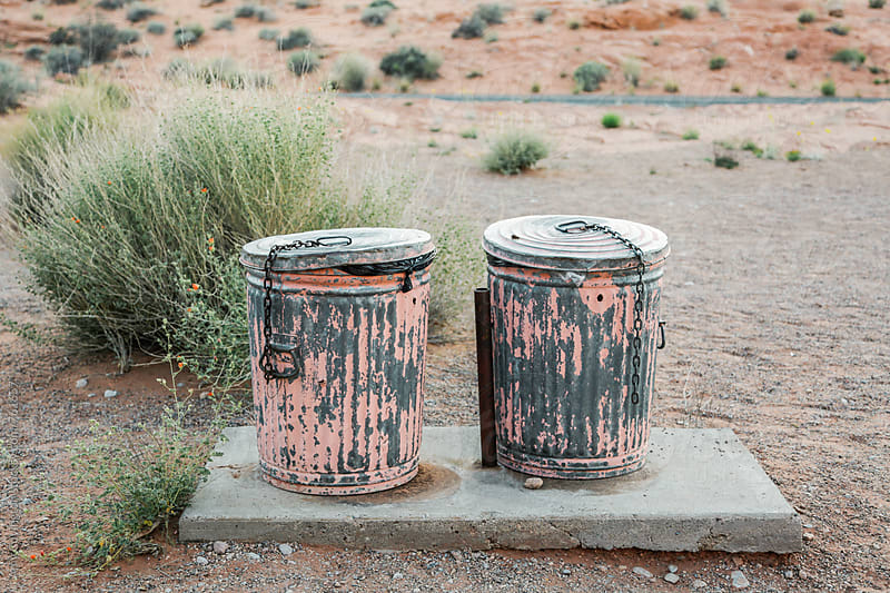 Two pink metal trash cans in the desert by Amy Covington for Stocksy United