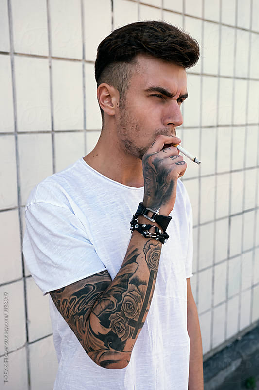 Serious bearded man with tattooed arms smoking cigarette by Danil Nevsky for Stocksy United