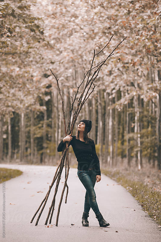 Woman collecting wood for winter on poplar forest. She is holding branches on a road. by BONNINSTUDIO for Stocksy United