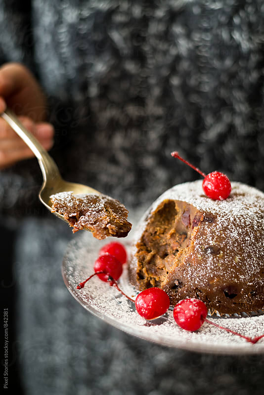 Christmas pudding served with cocktail cherries by Pixel Stories for Stocksy United