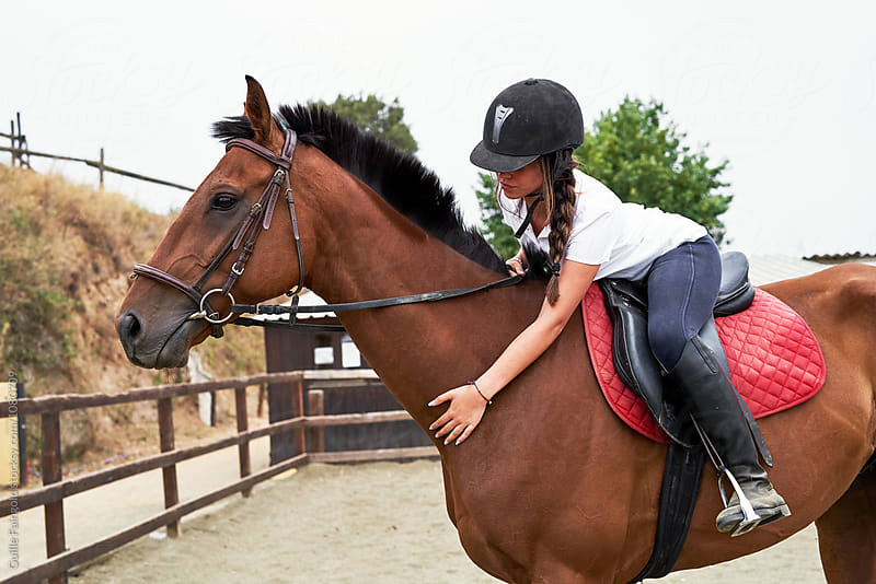 Young teen jockey stroking her horse while sitting in saddle by Guille Faingold for Stocksy United