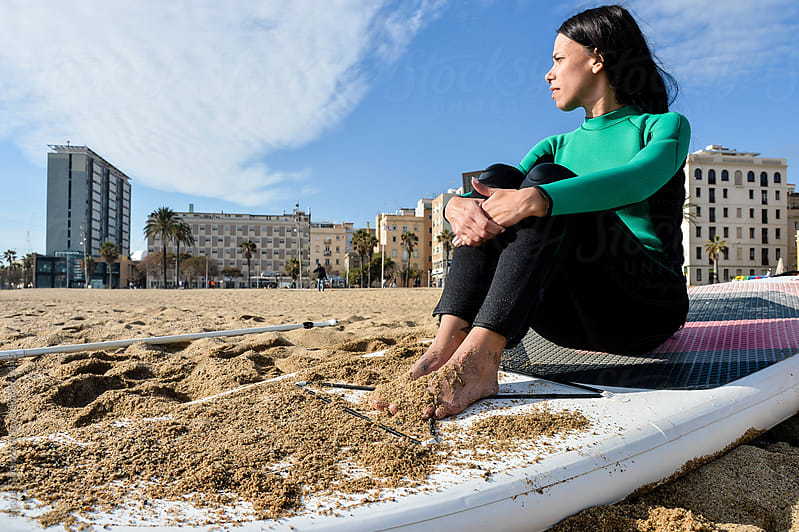 Woman sitting on her paddle board on the beach, Barcelona  by Bisual Studio for Stocksy United