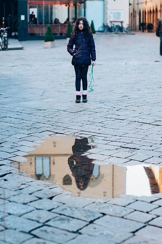 Girl's reflection in a puddle on the street by Beatrix Boros for Stocksy United