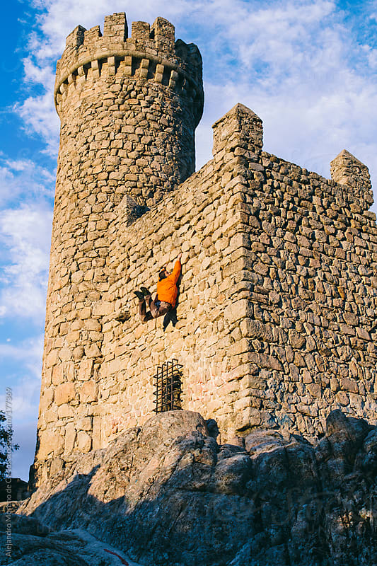 Young man climbing and having fun on a castle by Alejandro Moreno de Carlos for Stocksy United