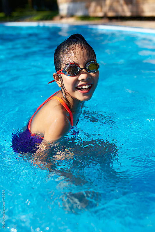 lovely little asian girl in swimming pool by Bo Bo for Stocksy United