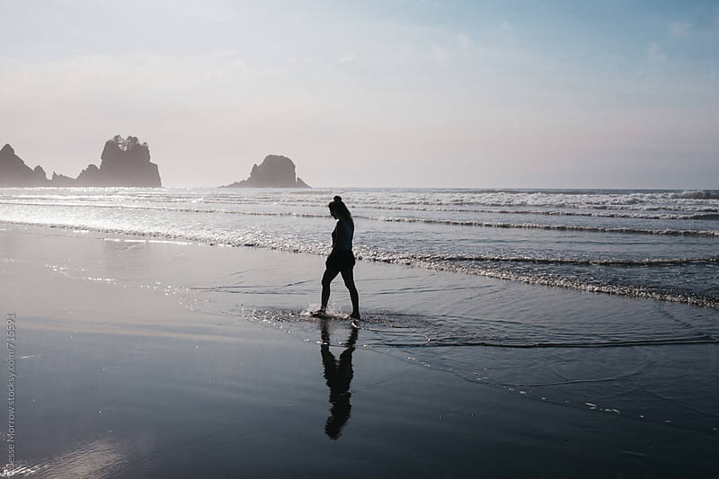 young female walks alone on beach with interesting rock formations by Jesse Morrow for Stocksy United
