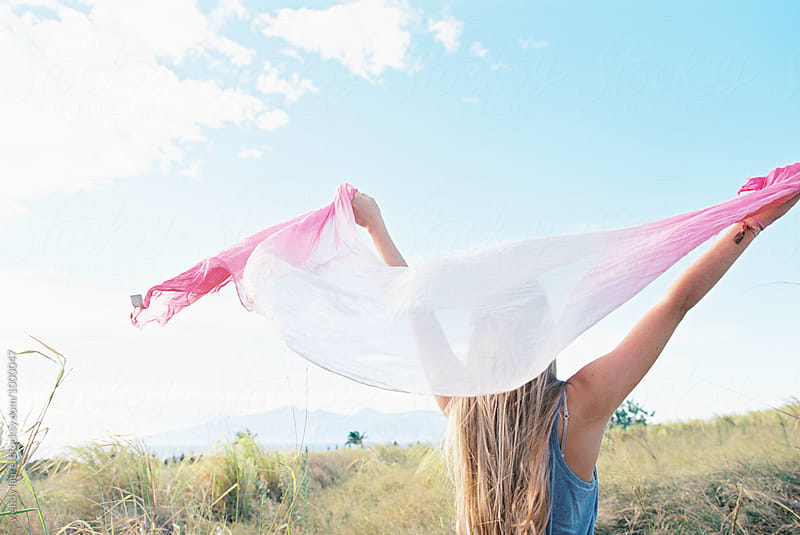 blonde girl holding pink scarf up against blue sky happy in joy by wendy laurel for Stocksy United