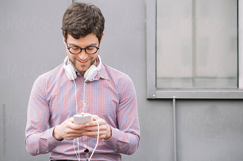Young man with headphone using his smartphone by Alberto Bogo for Stocksy United