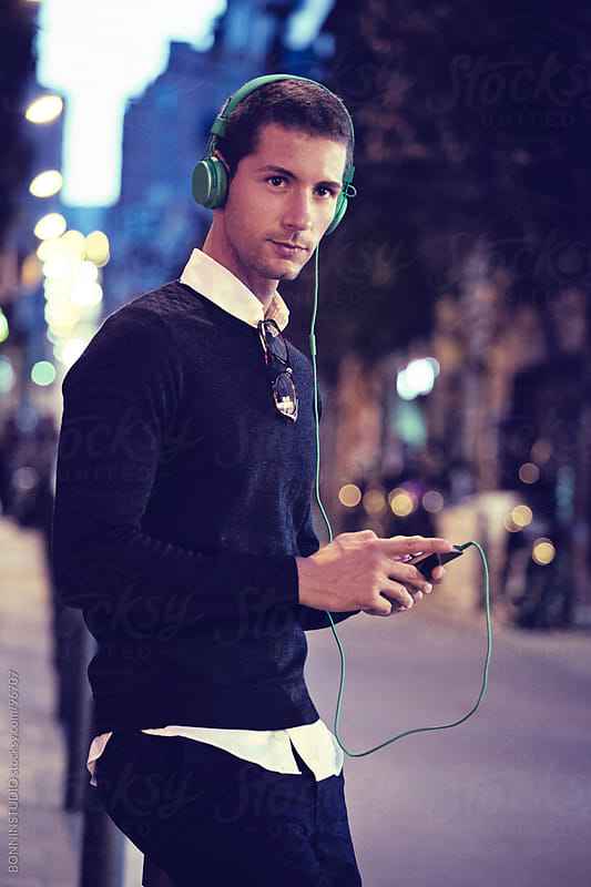 Modern casual man on the street. He is listening music on phone with headphones. by BONNINSTUDIO for Stocksy United