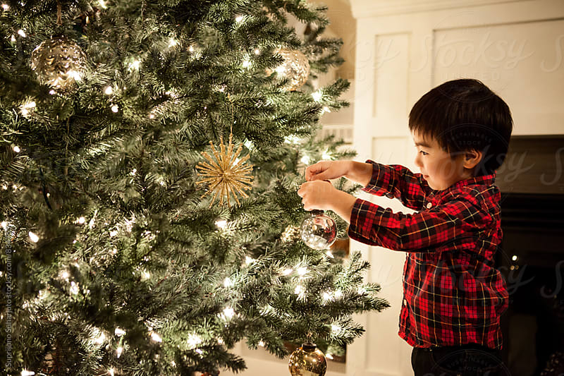 Cute Asian boy putting on ornament on a Christmas tree by Suprijono Suharjoto for Stocksy United