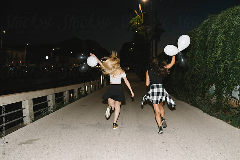 Women running in the city holding balloons by Simone Becchetti for Stocksy United