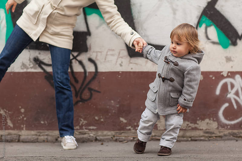 Boy Pulling His Mother's Hand on the Street by Mosuno for Stocksy United
