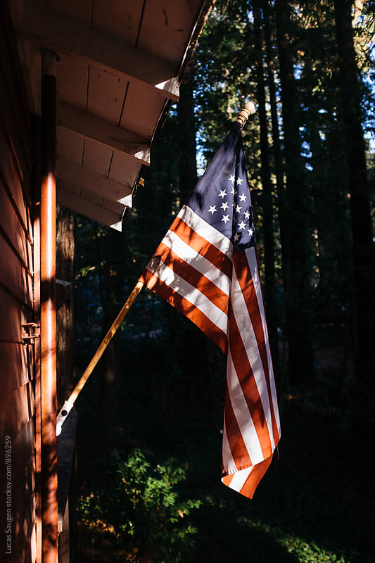 American flag hanging next to a cabin in the forest. by Lucas Saugen for Stocksy United