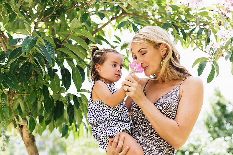 Mother smelling flower with daughter in park by Image Supply Co for Stocksy United