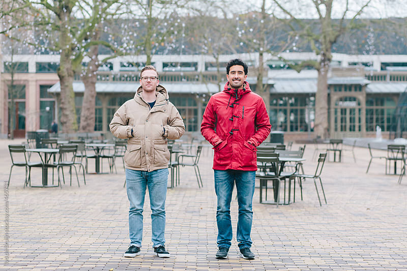 Two friends standing next to eachother looking at the camera by Ivo de Bruijn for Stocksy United