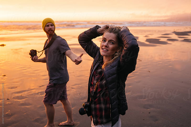 couple on beach during sunset by Jesse Morrow for Stocksy United