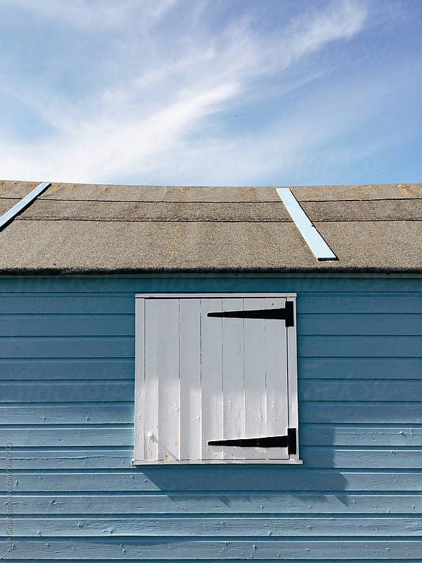White window shutter on a blue wooden panelled beach hut. Norfolk, UK. by Liam Grant for Stocksy United