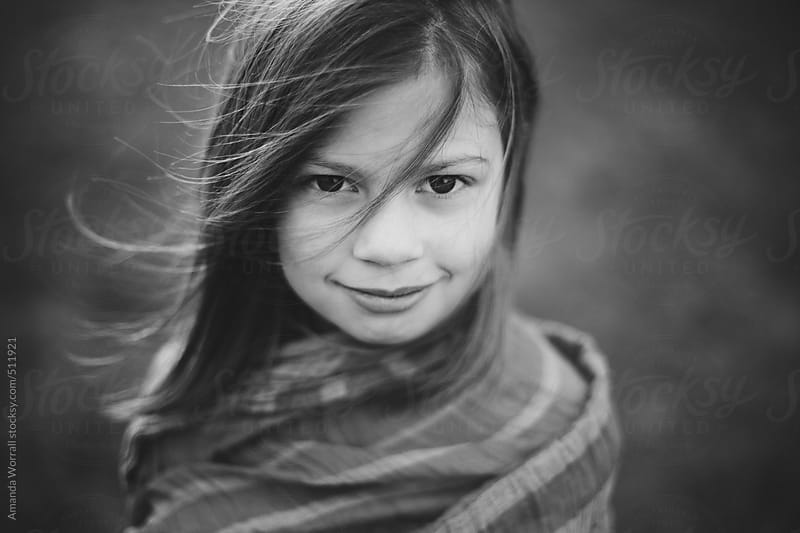 Black and white portrait of girl with windswept hair by Amanda Worrall for Stocksy United
