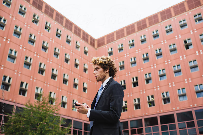 Man holding cell phone with buildings on the background by michela ravasio for Stocksy United