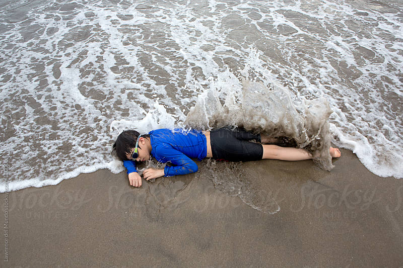 Young kid relaxing along the beach and enjoying the sand and the waves.  by Lawrence del Mundo for Stocksy United