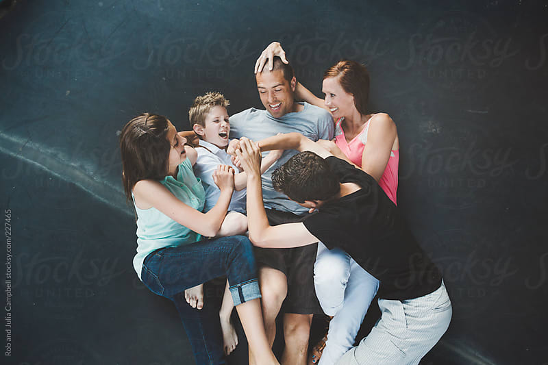 Young family with teenagers having fun wrestling on trampoline by Rob and Julia Campbell for Stocksy United