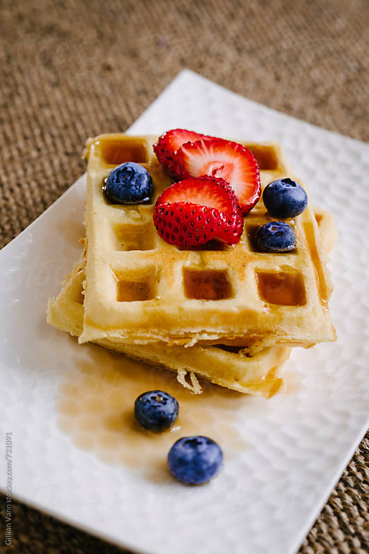freshly cooked waffles with fruit by Gillian Vann for Stocksy United