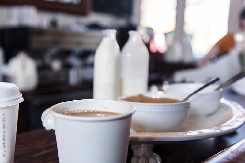 A cup of coffee sitting next to cream and Sugar on a countertop in a Coffee Shop. by Holly Clark for Stocksy United