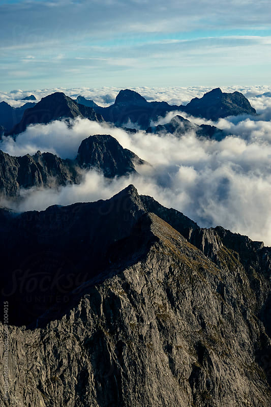 Sharp mountain peaks raising above the clouds in the south of new zealand in epic fashion. by Christian McLeod Photography for Stocksy United