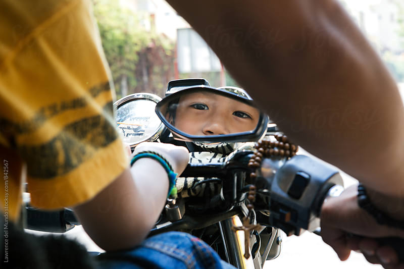 Young boy riding a motorcycle and looking at the camera through the side mirror by Lawrence del Mundo for Stocksy United