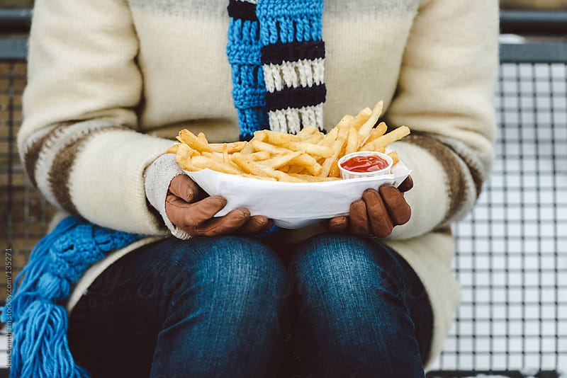 Woman eating french fries while skating by Jen Grantham for Stocksy United