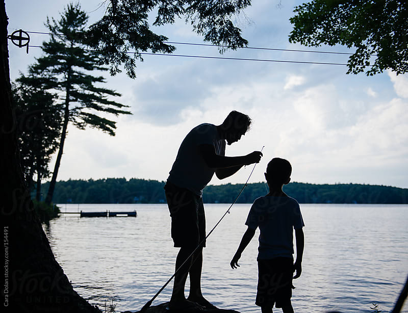 Dad helps son with his fishing pole by Cara Dolan for Stocksy United