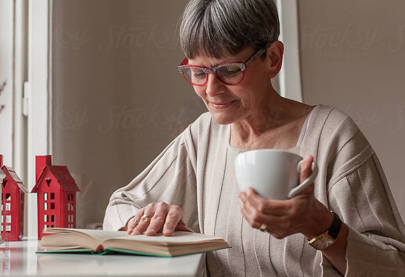 Senior Woman Reading a Book at Home by Mosuno for Stocksy United
