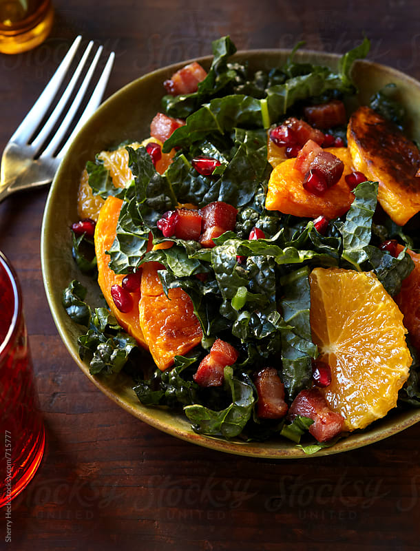Winter salad with kale, squash, oranges, and bacon by Sherry Heck for Stocksy United