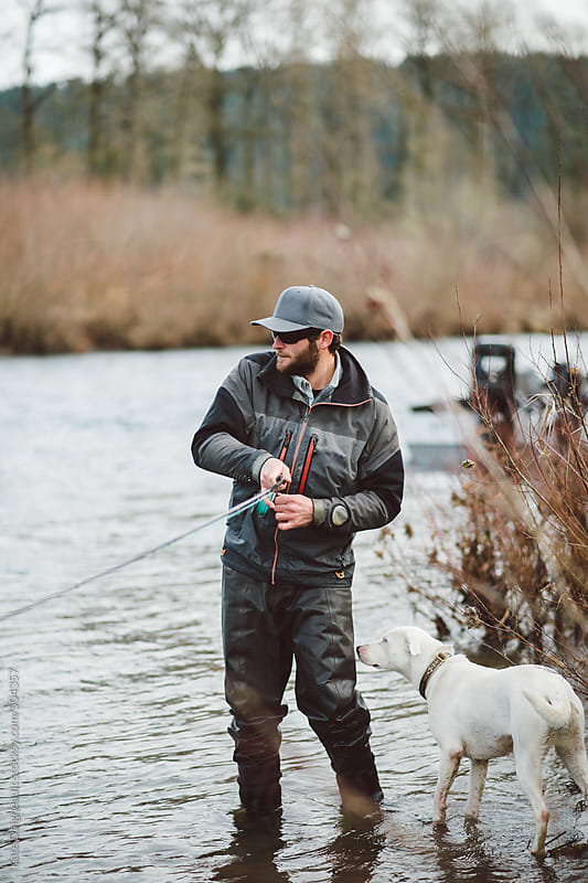 Fly fisherman and dog hooked up with fish in the river by Kate Daigneault for Stocksy United