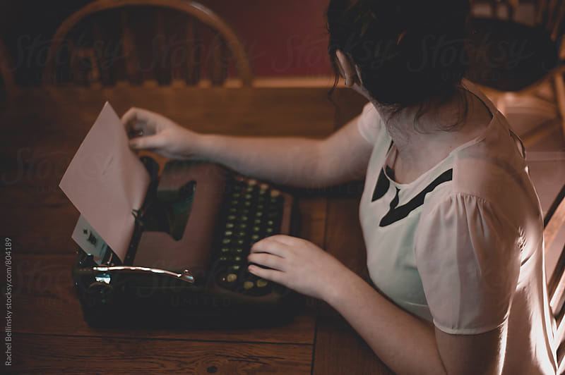 A young woman writes at an old fashioned typewriter by Rachel Bellinsky for Stocksy United
