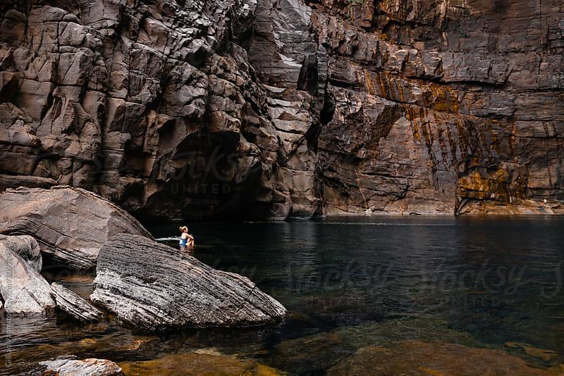 two sisters dwarfed by tall cliffs at Jim Jim Falls, Kakadu NP, NT, Australia by Gillian Vann for Stocksy United