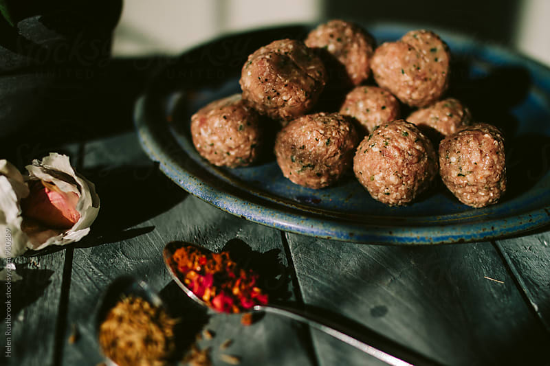 Uncooked meatballs and spices. by Helen Rushbrook for Stocksy United