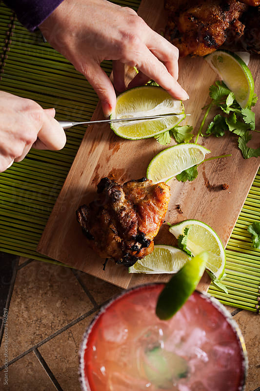 Fiesta: Woman Slicing Limes For Margaritas by Sean Locke for Stocksy United