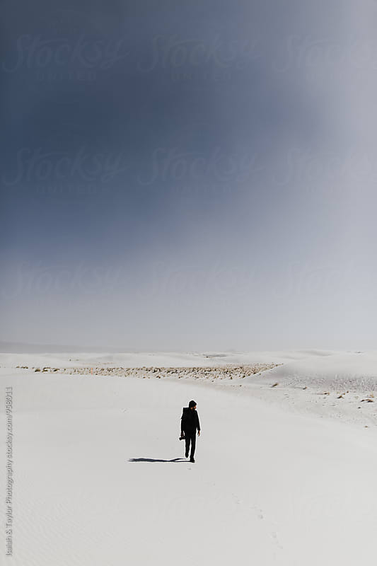 Man walking through desert landscape by Isaiah & Taylor Photography for Stocksy United