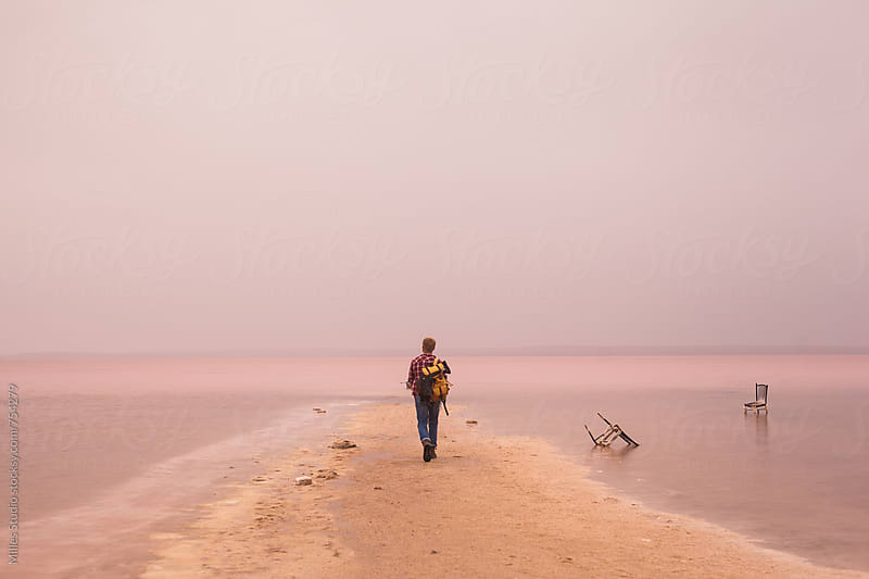 Tourist walking near pink lake by Milles Studio for Stocksy United
