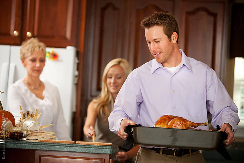 Thanksgiving: Father Takes Turkey Out of Oven by Sean Locke for Stocksy United