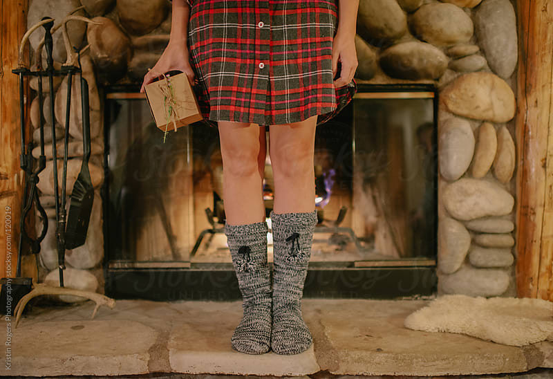 Woman standing on fireplace in pajamas with gift by Kristin Rogers Photography for Stocksy United