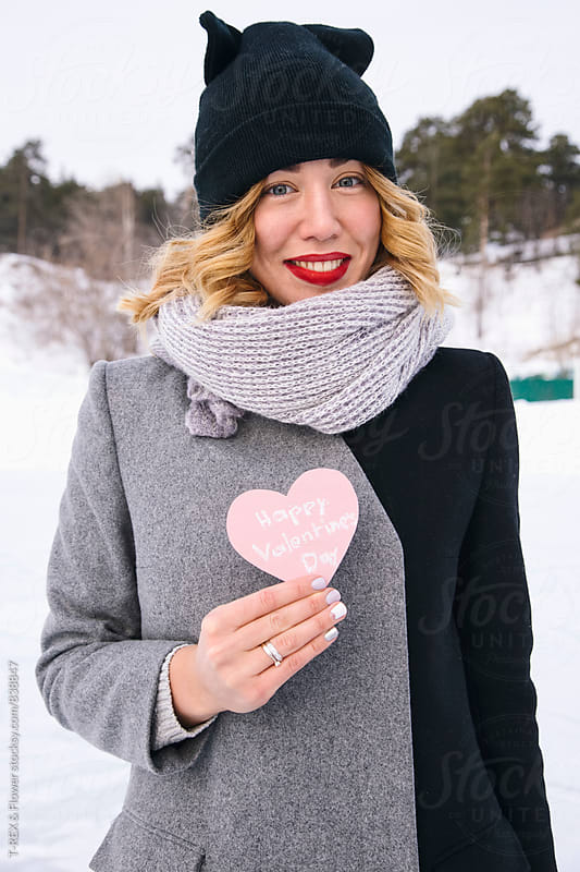 Portrait of young woman holding Valentine card by Danil Nevsky for Stocksy United