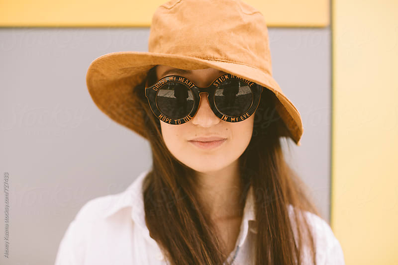 funny summer portrait of young woman with hat and round sunglasses by Alexey Kuzma for Stocksy United