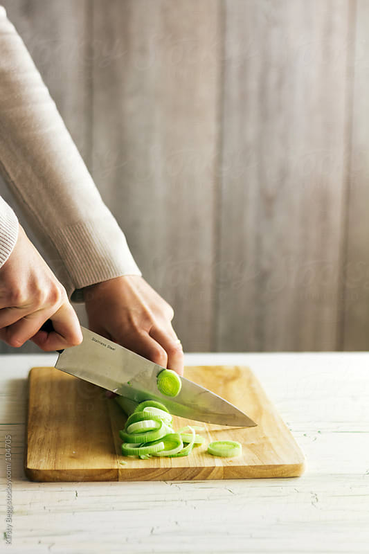 Woman chopping leeks for soup by Kirsty Begg for Stocksy United