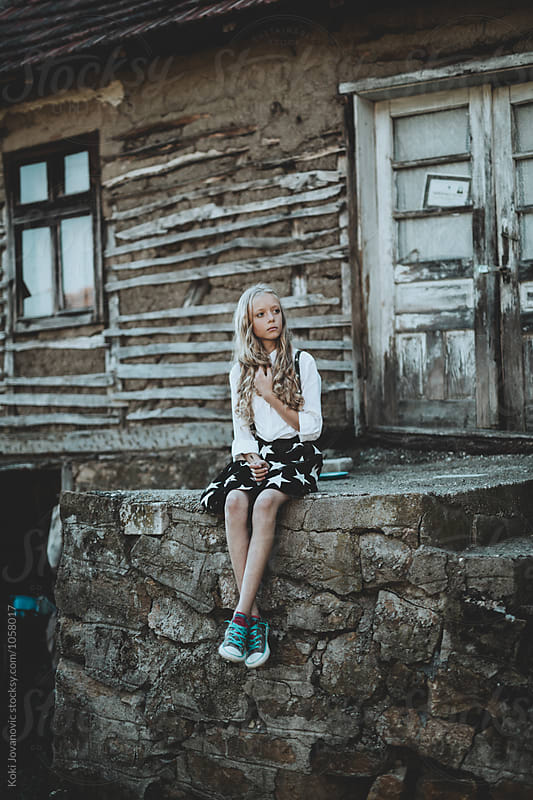 Little Girl sitting In Front Of old House by Koki Jovanovic for Stocksy United