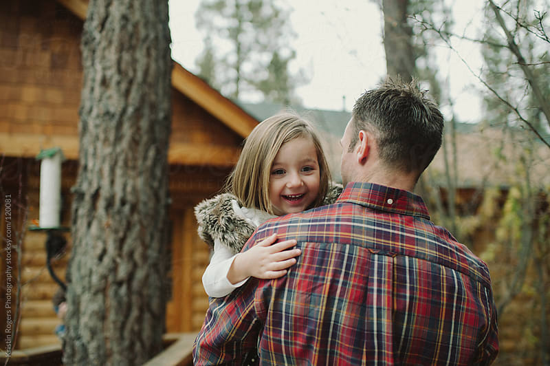 father carrying excited daughter into cabin by Kristin Rogers Photography for Stocksy United