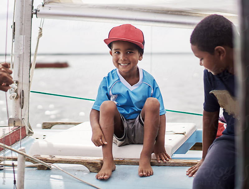 Two happy black brothers on a sailboat by Per Swantesson for Stocksy United
