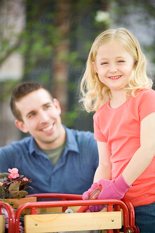 Planting: Little Girl Happy to Be Gardening with Dad by Sean Locke for Stocksy United