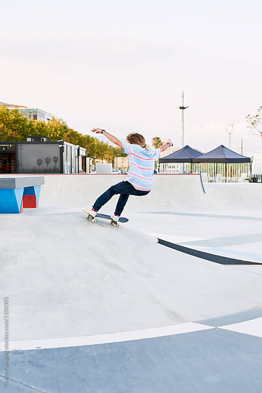 Back view of skater performing trick on hill in skate park by Guille Faingold for Stocksy United